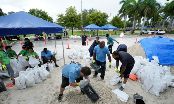 City workers fill sandbags at a drive-thru sandbag distribution event for residents ahead of the arrival of rains associated with tropical depression Fred, at Grapeland Park in Miami, Fla., on Aug. 13, 2021. (Wilfredo Lee/AP Photo)