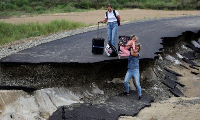 Tourists try to walk along a road damaged by flooding near the village of Tsybanobalka, Krasnodar region, Russia, on Aug. 14, 2021. (AP Photo)