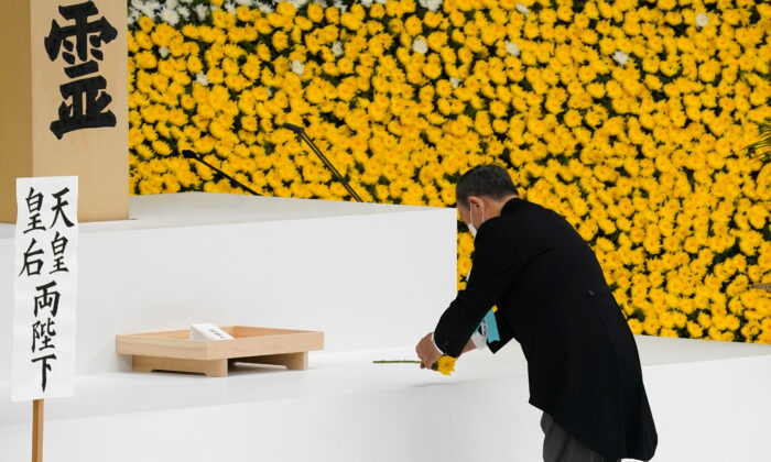Japanese Prime Minister Yoshihide Suga lays a flower during a memorial service marking the 76th anniversary of the end of World War II in Tokyo, Japan, on Aug. 15, 2021. (Toru Hanai/Pool via Reuters)