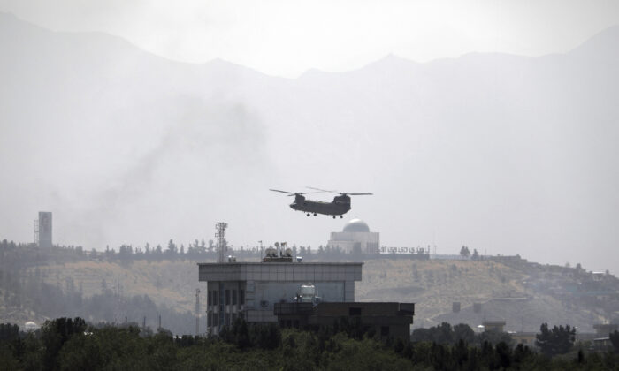 A U.S. Chinook helicopter flies over the U.S. Embassy, in Kabul, Afghanistan, on Aug. 15, 2021. (Rahmat Gul/AP Photo)