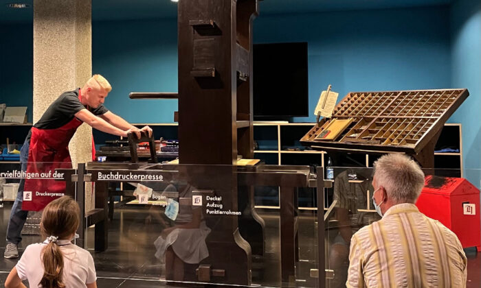 A docent in Mainz demonstrates to international visitors how the original Gutenberg printing press would have worked. (Lesley Sauls Frederikson)