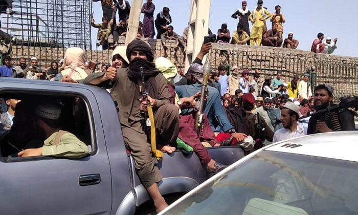 Members of the Taliban terrorist group sit on a vehicle along the street in Jalalabad, Afghanistan, on Aug. 15, 2021. (/AFP via Getty Images)
