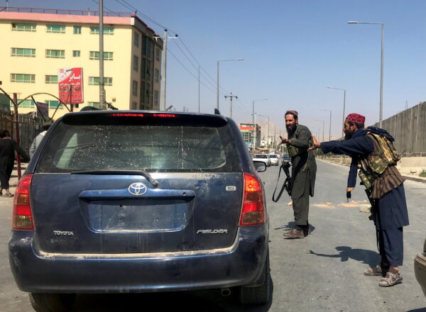 Members of Taliban forces gesture as they check a vehicle in Kabul