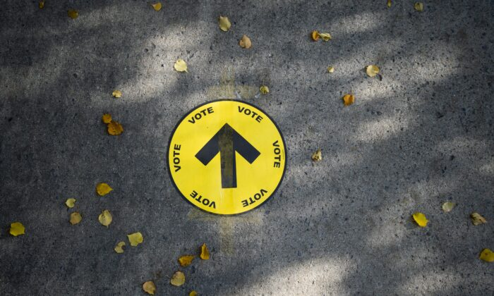 A sign directing voters to a polling station is taped to the sidewalk during the 2019 federal election, in Ottawa, on Oct. 21, 2019.  (The Canadian Press/Justin Tang)