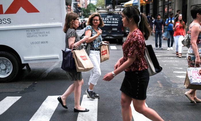 Shoppers walk along a street in New York City on July 5, 2019. (Spencer Platt/Getty Images)