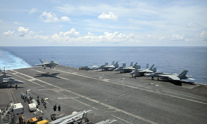 A U.S. Navy F/A-18 Super Hornets multirole fighter lands on the flight deck of the USS Ronald Reagan aircraft carrier as it sails in the South China Sea on its way to Singapore on Oct. 16, 2019.  (Catherine Lai/AFP via Getty Images)