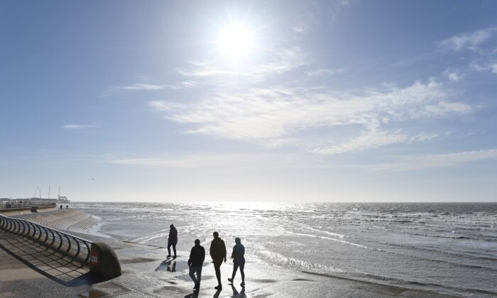 People enjoy the sunshine as they walk along the beach in Blackpool, Lancashire, United Kingdom on March 16, 2021. (Paul Ellis/AFP via Getty Images)
