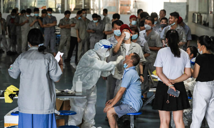A worker receives a COVID-19 test at the dining hall of a car parts factory in Wuhan, Hubei Province, on Aug. 4, 2021. (STR/AFP via Getty Images)