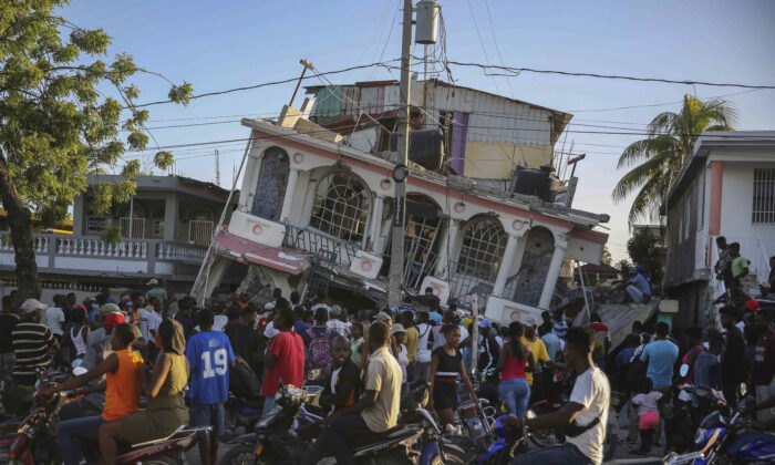 People gather outside the Petit Pas Hotel, destroyed by the earthquake in Les Cayes, Haiti on Aug. 14, 2021. (Joseph Odelyn/AP Photo)