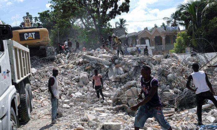 People remove debris at the collapsed Le Manguier hotel in Les Cayes, Haiti, on Aug. 16, 2021. (Matias Delacroix/AP Photo)