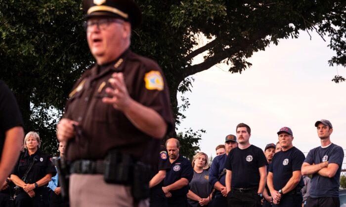 Emergency responders listen as Kalamazoo County Sheriff Richard Fuller talks briefly about Deputy Ryan Proxmire during a vigil outside the Sheriff's office in Kalamazoo, Mich., on Aug. 15, 2021. (Joel Bissell/Kalamazoo Gazette via AP)