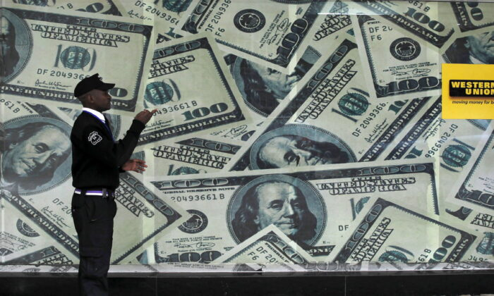 A security guard walks past a montage of old U.S. dollar bills outside a currency exchange in Nairobi, Kenya, on July 23, 2015. (Thomas Mukoya/Reuters)