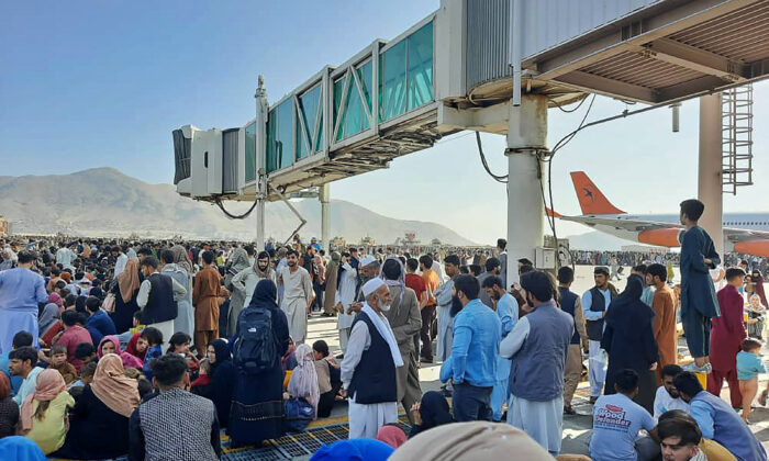 Afghans crowd at the tarmac of the airport in Kabul as they wait to flee Taliban control of Afghanistan after President Ashraf Ghani fled the country and conceded the insurgents had won the 20-year war on Aug. 16, 2021. (AFP via Getty Images)