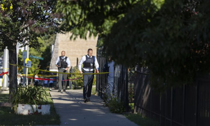Police investigate the scene where two young girls, 6 and 7, were shot in Chicago on Aug. 15, 2021. (Anthony Vazquez/Chicago Sun-Times via AP)