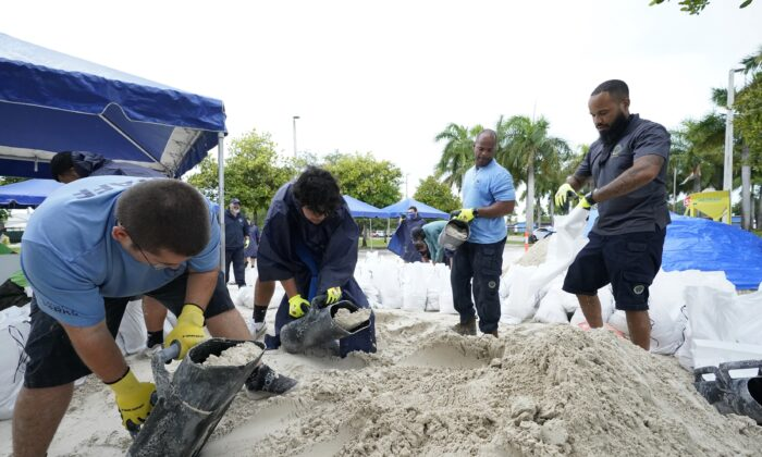 City workers fill sandbags at a drive-thru sandbag distribution event for residents ahead of the arrival of rains associated with Tropical Storm Fred, at Grapeland Park in Miami, Fla., on Aug. 13, 2021. (Wilfredo Lee/AP Photo)