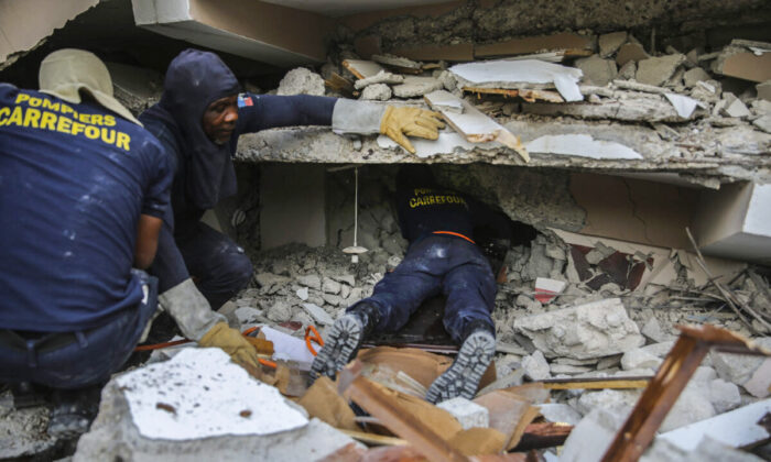 Firefighters search for survivors inside a collapsed building, after the Aug. 14 7.2 magnitude earthquake in Les Cayes, Haiti, Sunday, Aug. 15, 2021. (AP Photo/Joseph Odelyn)