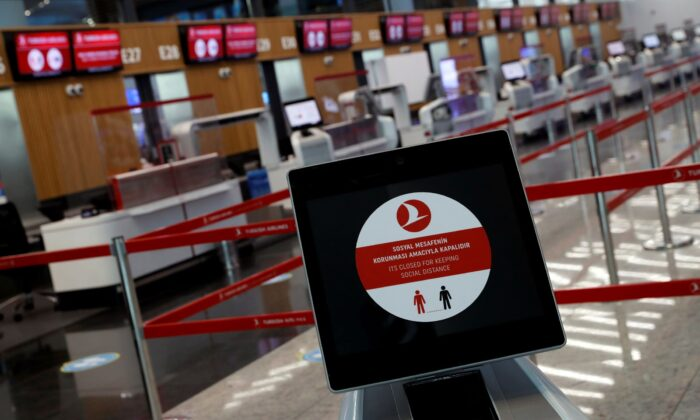 A social distancing sign is seen before check-in counters in Turkey, on June 19, 2020. (Murad Sezer/Reuters)