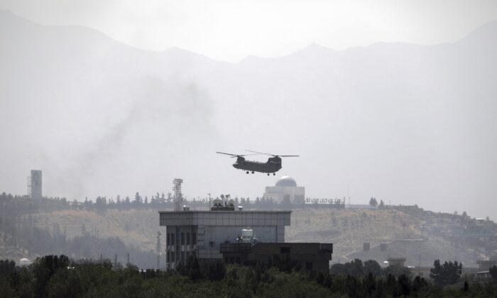 A U.S. Chinook helicopter flies over the U.S. Embassy in Kabul, Afghanistan, on Aug. 15, 2021. (Rahmat Gul/AP Photo)