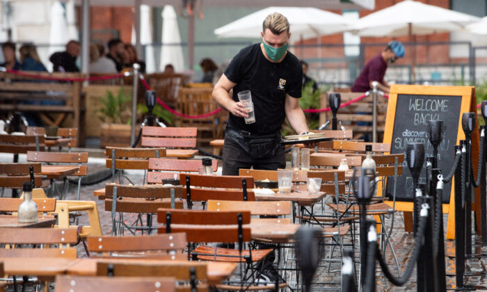 A waiters clears empty outside tables following a downpour of rain in Covent Garden, London, on July 4, 2021. (Dominic Lipinski/PA)
