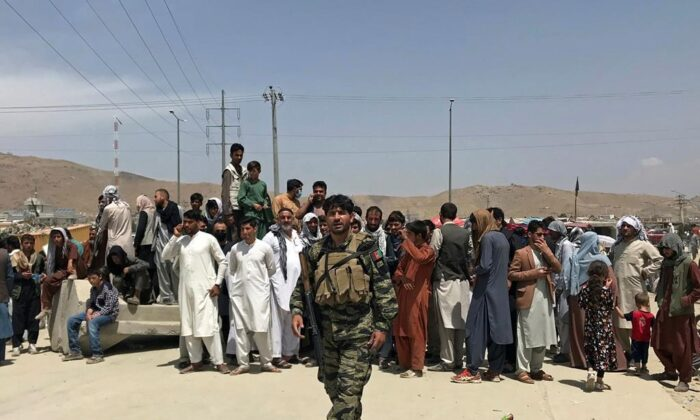 """Hundreds of people gather outside the international airport in Kabul, Afghanistan, Aug. 17, 2021. The Taliban declared an """"amnesty"""" across Afghanistan and urged women to join their government Tuesday, seeking to convince a wary population that they have changed a day after deadly chaos gripped the main airport as desperate crowds tried to flee the country. (AP Photo)"""