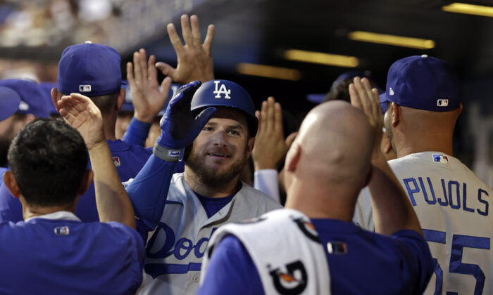Los Angeles Dodgers' Max Muncy celebrates a two-run home run in the dugout during the second inning of a baseball game against the New York Mets in New York on Aug. 15, 2021. (AP Photo/Adam Hunger)
