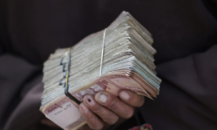 A money changer holds a stack of Afghan currency on a street in central Kabul on April 2, 2014. (Tim Wimborne/Reuters)