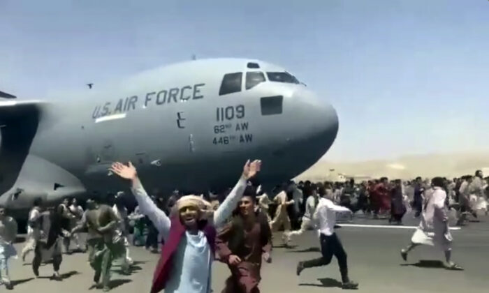 Hundreds of people run alongside a U.S. Air Force C-17 transport plane as it moves down a runway  of the international airport, in Kabul, Afghanistan, on Aug. 16. 2021. (Verified UGC via AP)