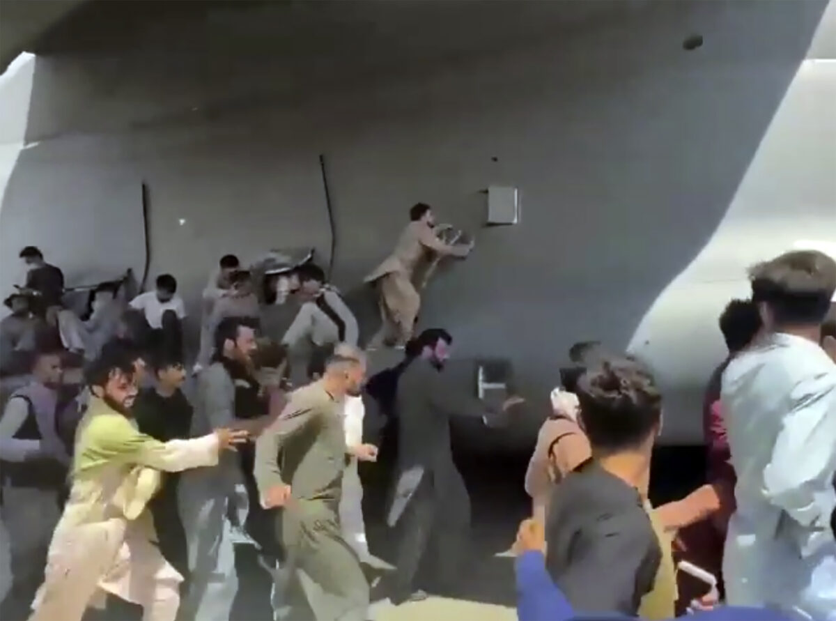 Afghans cling to plane