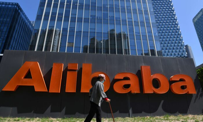 A woman walks past an Alibaba sign outside the company's office in Beijing, on April 13, 2021. (Greg Baker/AFP via Getty Images)