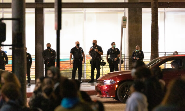Los Angeles Police Officers assembled across the street as protestors gather in front of a Chase Bank building on the corner of Sunset Blvd. and Vine St., in Los Angeles, Calif., on April 16, 2021. (John Fredricks/The Epoch Times)