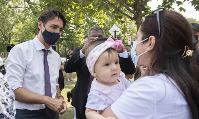 Liberal Leader Justin Trudeau talks with a family following a child-care funding announcement in Montreal on Aug. 5, 2021. (The Canadian Press/Graham Hughes)