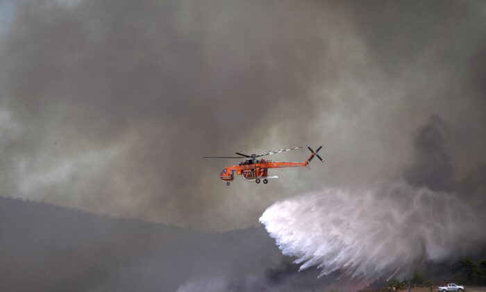 An helicopter drops water over a fire in Siderina village helicopter about 55 kilometers (34 miles) south of Athens, Greece, on Aug. 16, 2021. (Thanassis Stavrakis/AP Photo)