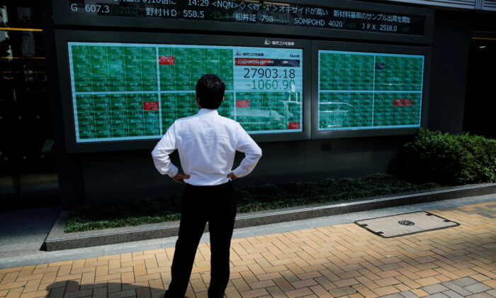 A man watches an electric board showing the Nikkei index outside a brokerage at a business district in Tokyo, Japan, on June 21, 2021. (Kim Kyung-Hoon/Reuters)