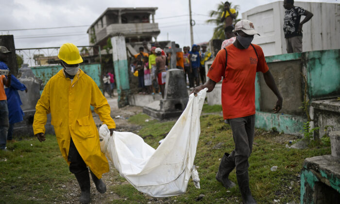 Men carry the body of a boy that was found in collapsed building lies at the back of a truck at the entrance of the cemetery in Les Cayes, Haiti, on Aug. 17, 2021. (Matias Delacroix/AP Photo)