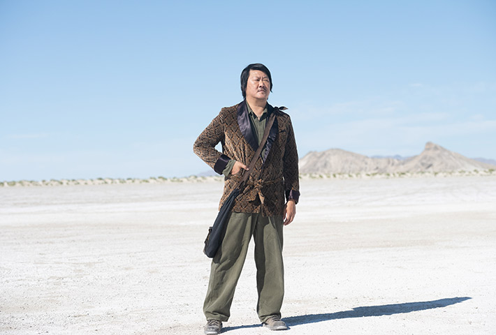 man in brown jacket and green pants standing in the desert in NINE DAYS