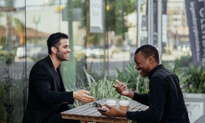 Two men having a conversation. (Pexels)