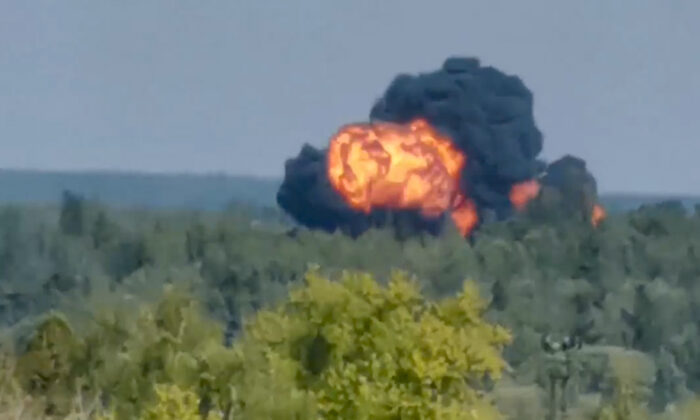 In this handout photo taken from video, flame and smoke rise from the place where the new light military transport plane Il-112V crashes near Kubinka airfield about 45 kilometers (28 miles) west of Moscow, Russia, on Aug. 17, 2021. (Dmitry Ovchinnikov via AP)