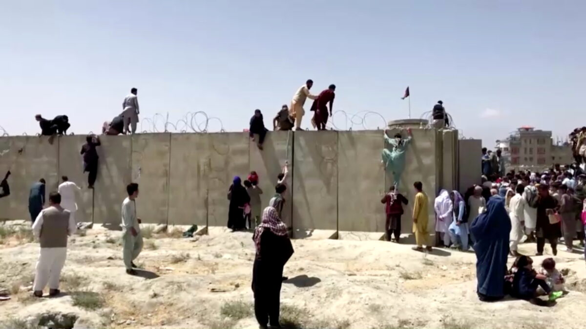 People climb a barbed wire wall