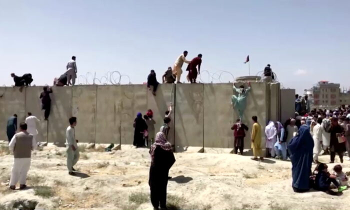 People climb a barbed wire wall to enter the airport in Kabul, Afghanistan August 16, 2021, in this still image taken from a video. (Reuters TV/via Reuters)