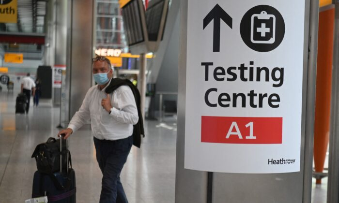A passenger walks past signage displaying the way to a COVID-19 test centre, in Terminal 5 at Heathrow airport in London, on June 3, 2021. (Daniel Leal-Olivas/AFP via Getty Images)