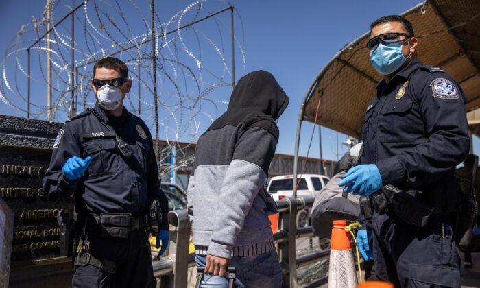 Asylum seekers pass U.S. Customs and Border Protection officers while crossing an international bridge from Mexico into the United States in Ciudad Juarez, Mexico, on March 17, 2021. (John Moore/Getty Images)