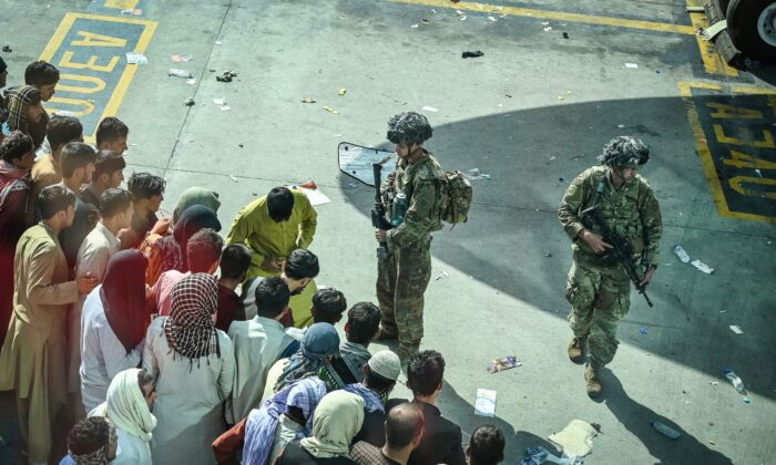 US soldiers stand guard as Afghan people wait at the Kabul airport in Kabul, Afghanistan on Aug. 16, 2021. (Wakil Kohsar/AFP via Getty Images)