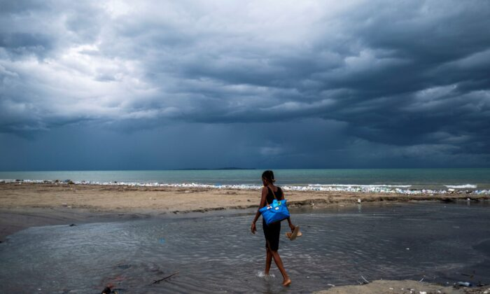 A woman wades through the water, as Tropical depression Grace approaches, after Saturday's 7.2 magnitude quake, in Les Cayes, Haiti, on Aug. 16, 2021. (Ricardo Arduengo/Reuters)