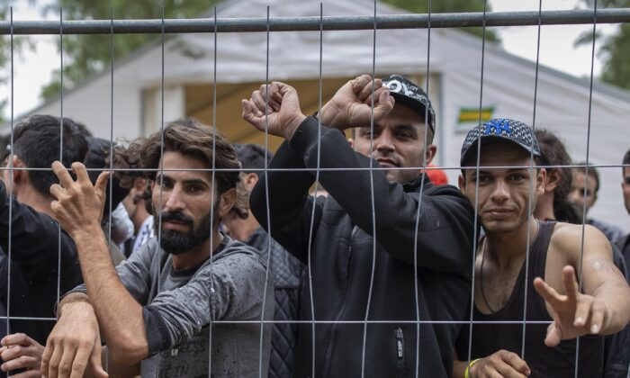 Illegal immigrants stand behind a fence inside the newly built refugee camp in the Rudninkai military training ground, some 38 kilometers (23.6 miles) south from Vilnius, Lithuania, on Aug. 4, 2021. (Mindaugas Kulbis/AP Photo)