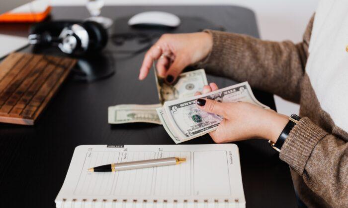 A person counting cash. (Karolina Grabowska/Pexels)