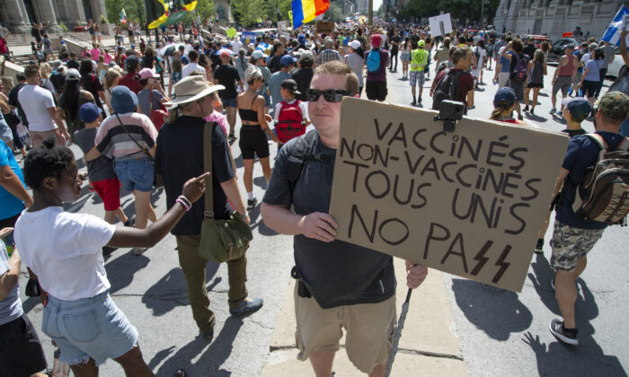 Protesters march during a demonstration against Quebec's decision to impose a vaccination passport for non-essential businesses and services, in Montreal on Aug. 14, 2021. (The Canadian Press/Peter McCabe)