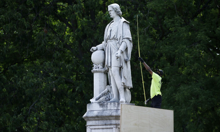 A city worker measures the statue of Christopher Columbus at Marconi Plaza as they build a cover in the South Philadelphia neighborhood of Philadelphia, Pa., on June 16, 2020. (Matt Slocum/AP Photo)