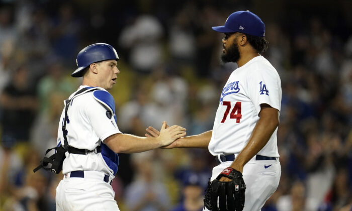 Los Angeles Dodgers catcher Will Smith and relief pitcher Kenley Jansen (74) celebrate the team's 4-3 win over the Pittsburgh Pirates in a baseball game in Los Angeles on Aug. 17, 2021. (AP Photo/Marcio Jose Sanchez)