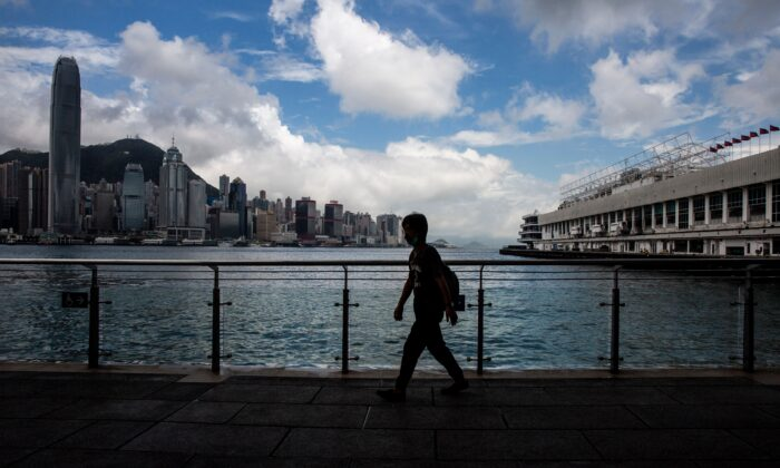 A man walks along Victoria Harbour in the Kowloon district of Hong Kong on Aug. 16, 2021.  (Isaac Lawrence/AFP via Getty Images)