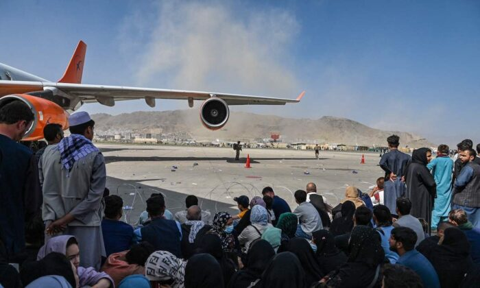 Afghan people sit as they wait to leave Kabul airport on Aug. 16, 2021. After a stunningly swift end to Afghanistan's 20-year war, thousands of people mobbed the city's airport trying to flee Taliban terrorists. (Wakil Kohsar/AFP via Getty Images)
